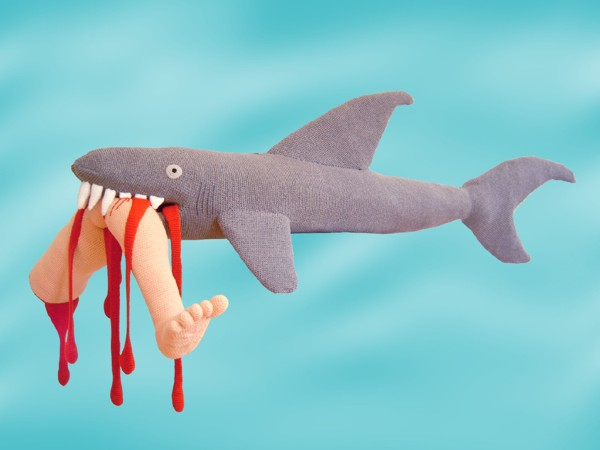 tiburon de peluche con mano de hombre